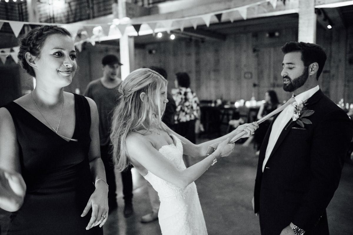 bride-pulling-grooms-tie Becky and Alex   Green Door Gourmet - Fall Nashville Wedding