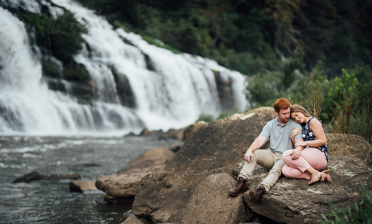 cuddling-in-front-of-waterfall Rock Island State Park Engagement Photos